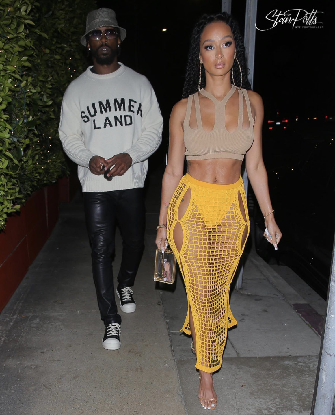 Draya Michele Spotted in Dion Lee Tan Knit Cutout Crop Top and Yellow Crochet Skirt During Outing With Tyrod Taylor in Nahmias Sweater, 1017 ALYX 9SM Black Leather Pants, Celine Plaid Bucket Hat and Rick Owens Sneakers