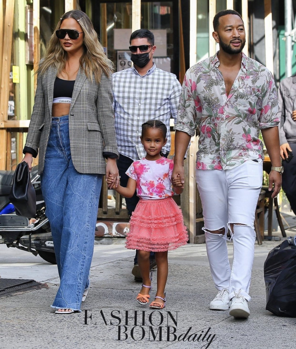 Chrissy Teigen Spotted on Family Outing in SoHo With John Legend and Daughter Luna Wearing Casual-Chic Look Including Saint Laurent Checked Blazer, Calvin Klein Black Logo Bralette, Dries Van Noten Wide Leg Jeans, and Bottega Veneta Accessories