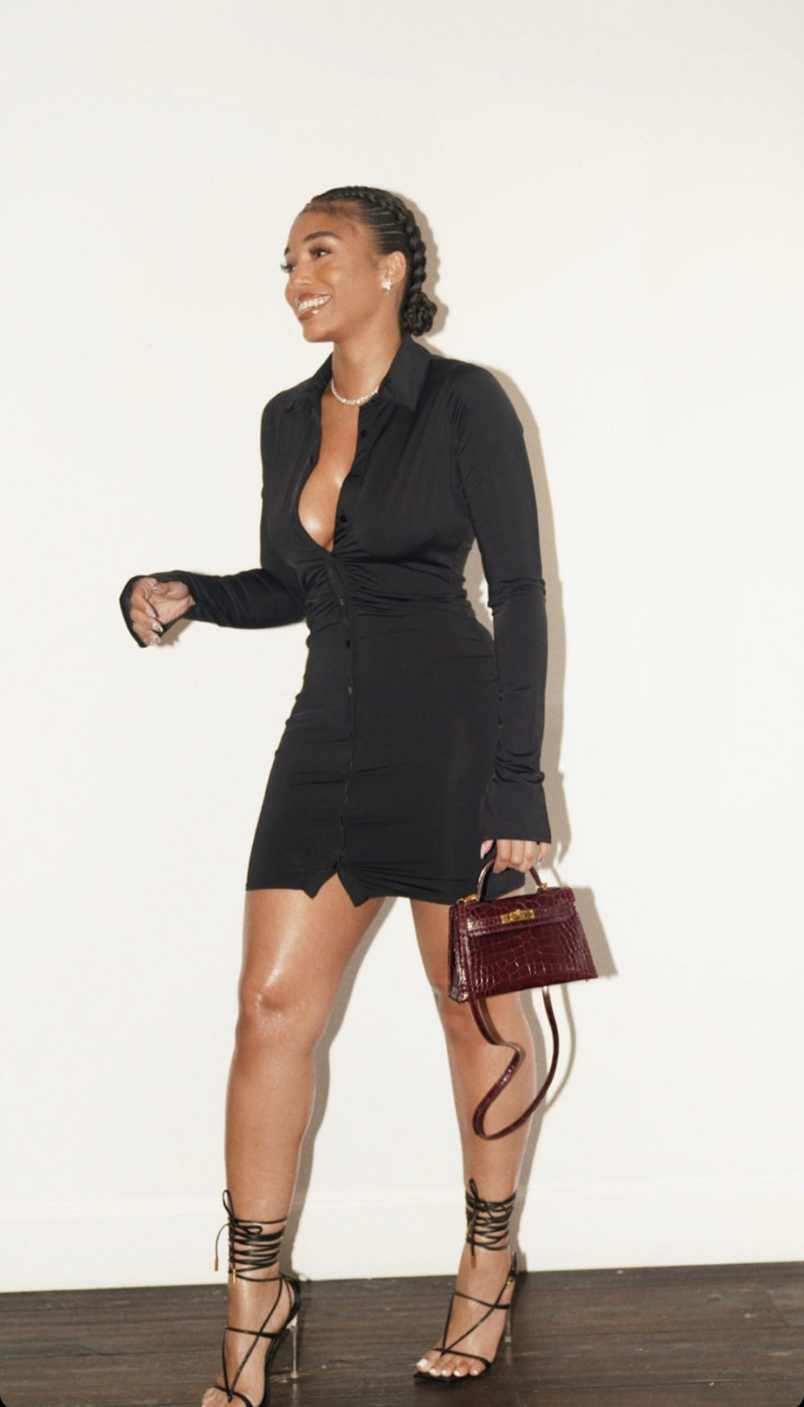 Lori Harvey Flashes Her Smile Wearing With Jean Black Ruched Button Shirt Dress Paired With Hermès Burgundy Croc Handbag and Versace Black Lace-Up Sandals